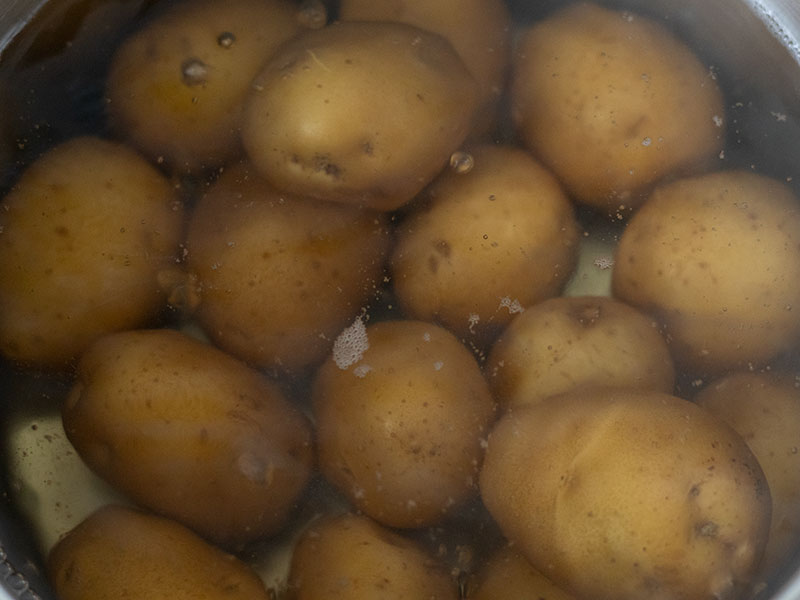 Baby potatoes in boiling water on stove.