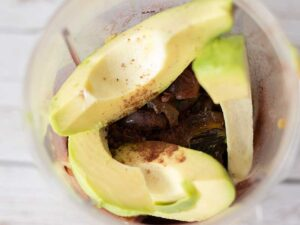 Whole, clean, natural ingredients in a blender for making homemade avocado mousse.