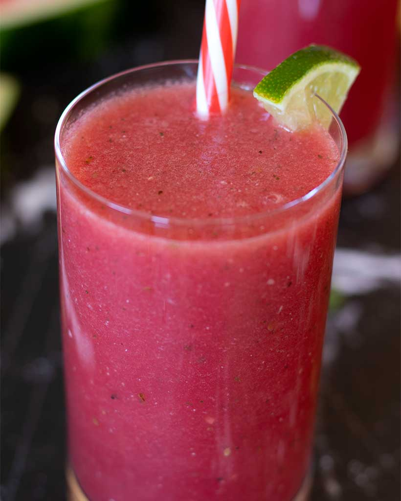 Tasty watermelon smoothie without yogurt in a big glass with straw decorated with fresh lime.