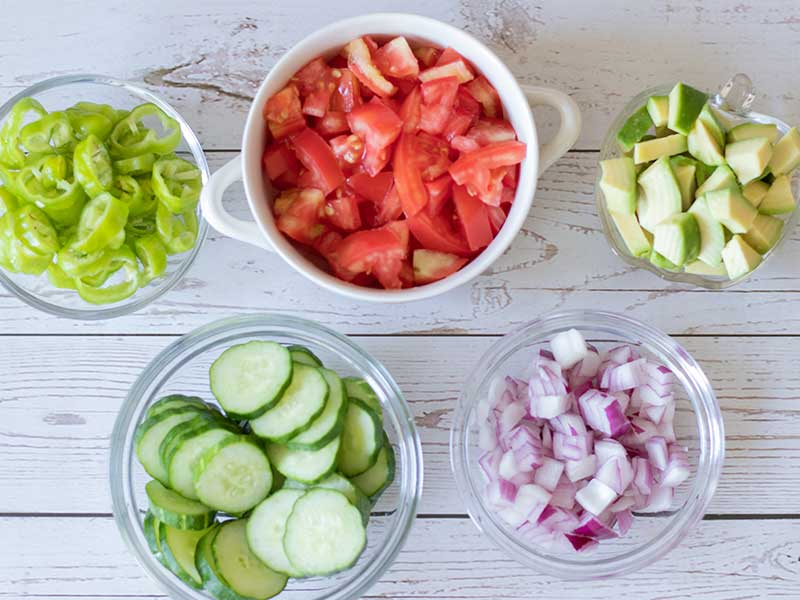 Fresh chopped vegetables (tomatoes, cucumbers, red onion, Shishito peppers and avocado) for preparing healthy, plant-based, gluten free salad