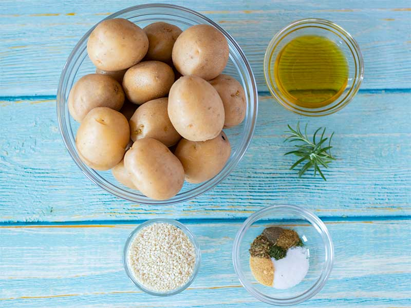 Plant-based, wholesome minimal ingredients new baby potatoes recipe for lunch or dinner: small potatoes, olive oil, fresh rosemary, spices and herbs..