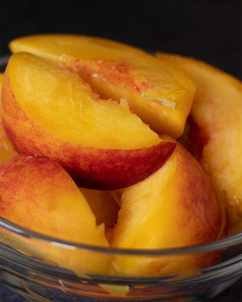 Fresh sliced peaches with skin prepared for making delicious vegan smoothie recipe without banana.