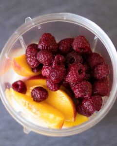 Real food wholesome ingredients for vegan peach and raspberry smoothie recipe.