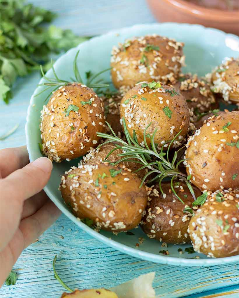 Crispy, golden new potatoes with rosemary, sesame seeds and other herbs for healthy, vegan or vegetarian side dish. Kid friendly meal prep.