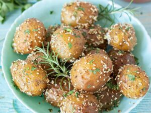 Freshly roasted whole baby potatoes in oven decorated with rosemary.