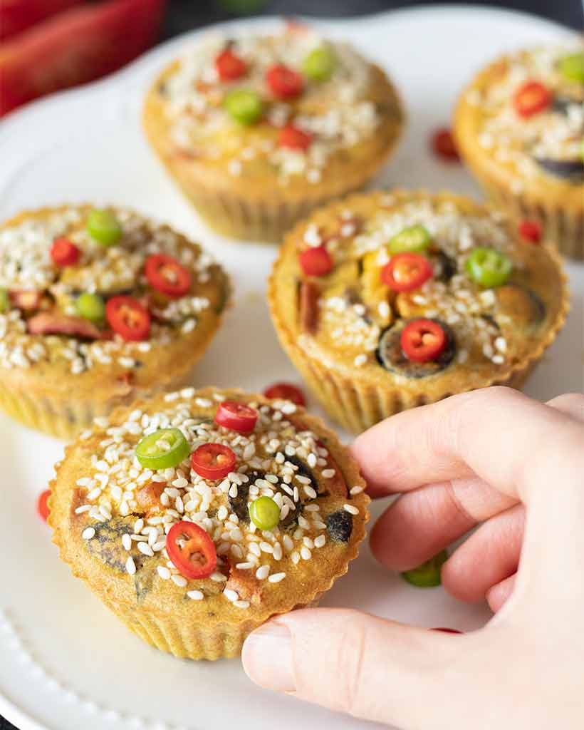 Woman's hand reaching to take yummy, easy-to-make, gluten-free chickpea flour muffins for breakfast.