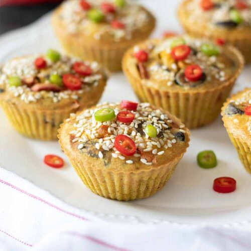 Mini chickpea flour frittatas, vegan-friendly savoury breakfast or snack decorated with sesame seeds and finely chopped red and green peppers on white plate.