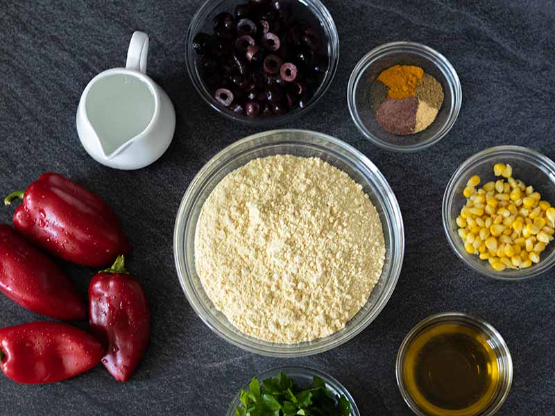 Plant-based-simple ingredients for baking no-yeast savoury muffins in tins.  Olives, chickpea flour, olive oil, water, red peppers, fresh parsley, corn and spices.