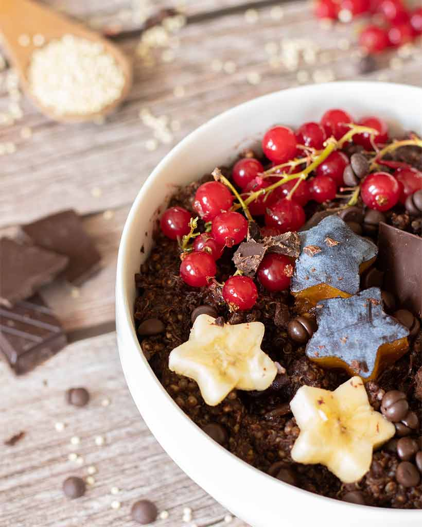 A close up of healthy chocolate quinoa porridge decorated with vegan dark chocolate squares and chips, banana, plums and red currants. Easy kid-friendly breakfast or dessert idea.