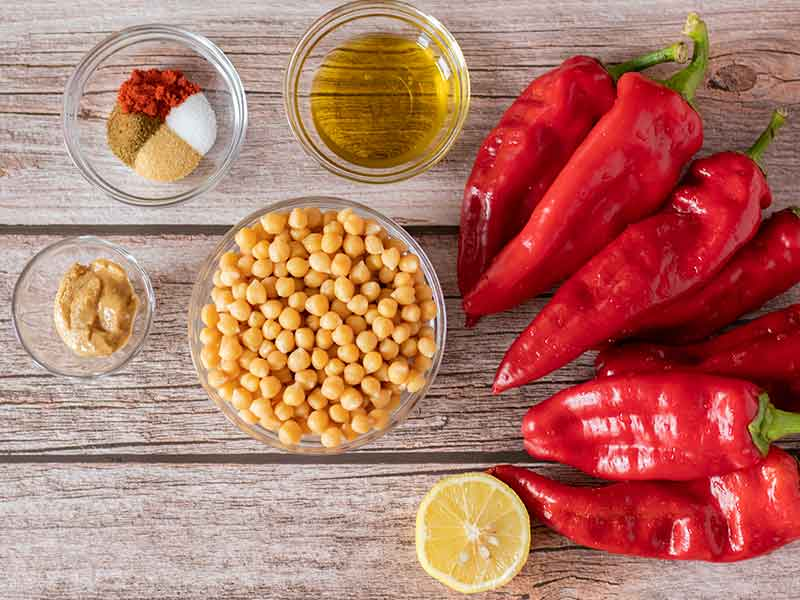 Wholesome, plant-based, clean eating ingredients for preparing homemade vegetarian hummus: roasted red peppers, chickpeas (garbanzo beans), olive oil, lemon juice, tahini and spices.
