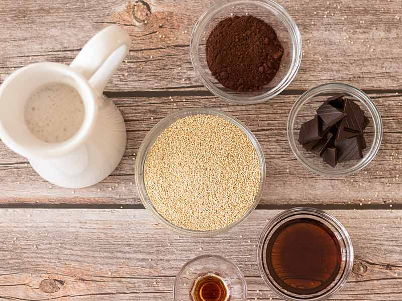 Wholesome, plant-based ingredients for preparing delicious, sweet gluten-free dish: white quinoa, maple syrup, almond milk, dark chocolate, cacao powder and pure vanilla extract.