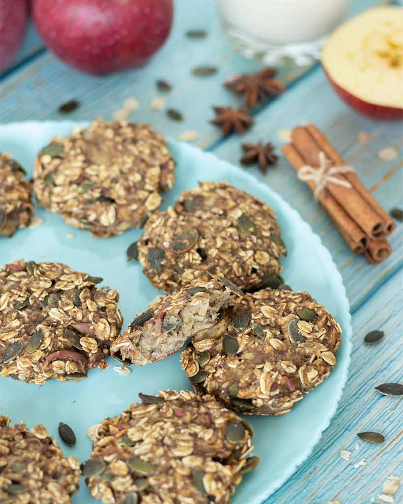 Soft and chewy apple oatmeal cookies with cinnamon on plate with blue wooden table for a healthy breakfast.