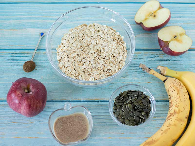 Simple and wholesome ingredients for baking delicious and soft apple cookies with pumpkin seeds: red Delicious, oats, bananas, pumpkin seeds, cinnamon and homemade flax egg.